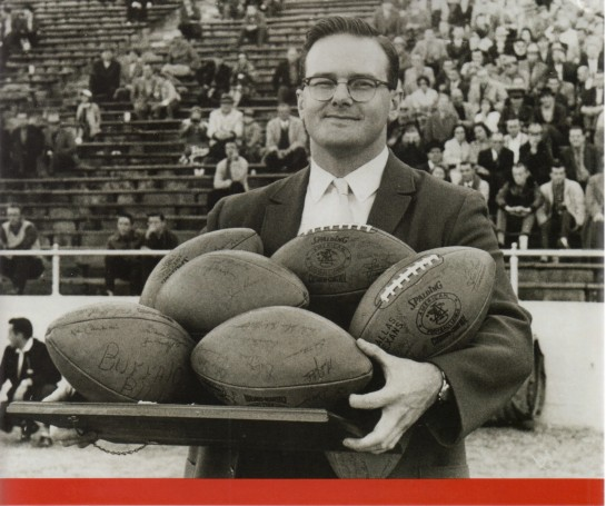 AFL and Kansas City Chief founder Lamar Hunt holding a platter of AFL footballs.