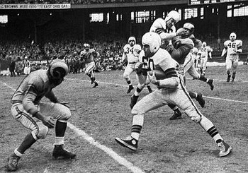Hall of Fame quarterback Otto Graham tries to avoid a Ram defende in the 1950 NFL Title Game.
